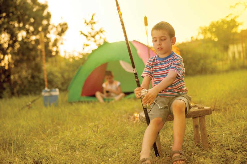 露营中学习使用钓鱼竿的小男孩