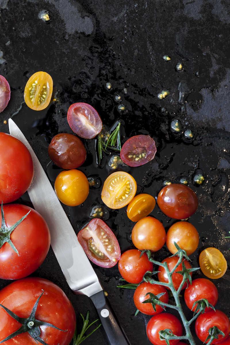 黑色背景上的新鲜番茄和切开的番茄