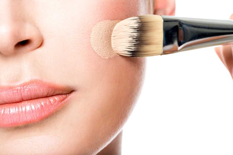 在脸上涂抹粉底的化妆模特