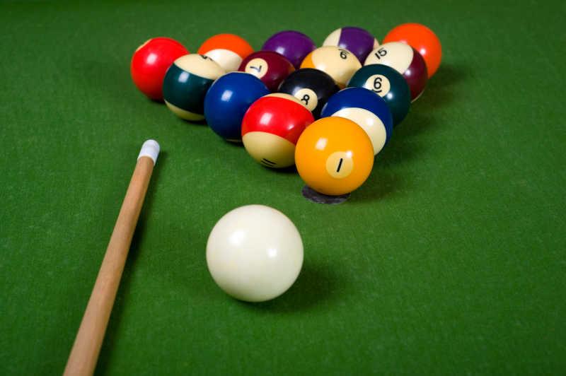 绿色台球桌上的球杆与摆好的球