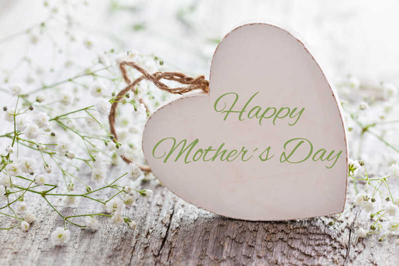 心形木牌上的母亲节快乐文字和白的花朵