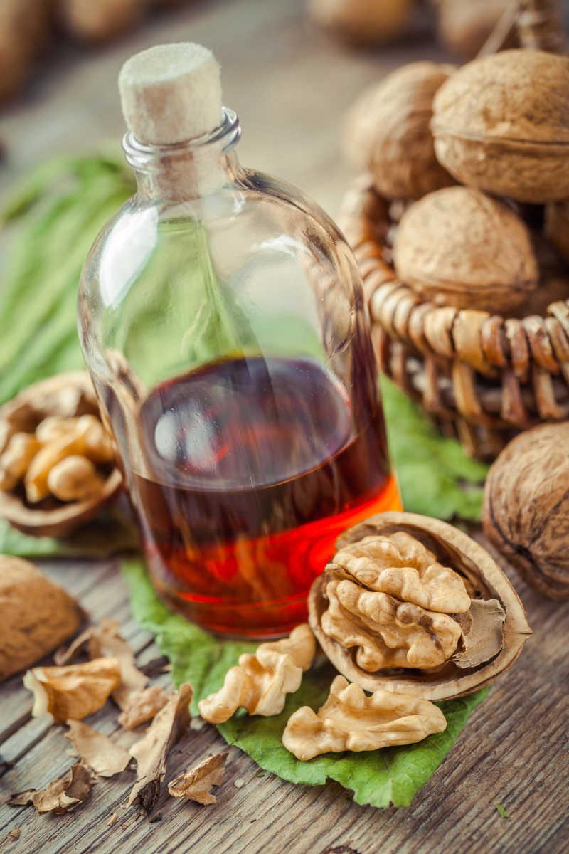 旧厨房餐桌上的核桃瓶装酊剂油或坚果篮子