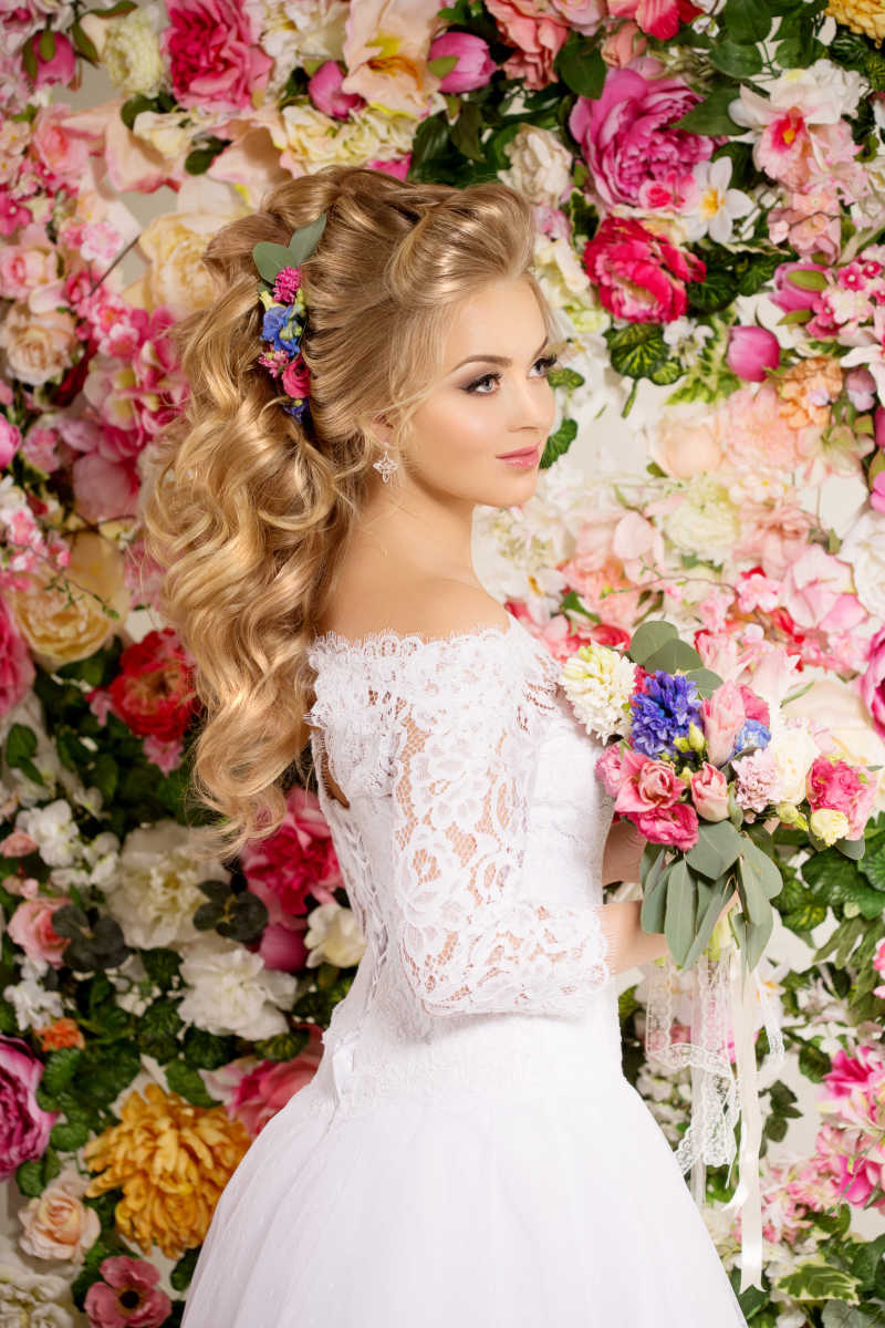 花墙前拿着手捧花的美丽新娘侧面特写