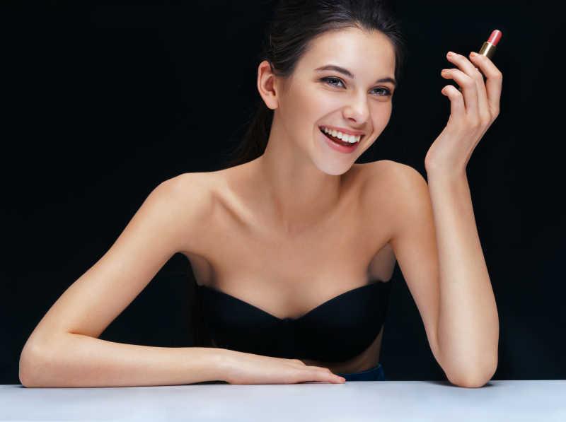 黑色背景下的快乐的黑发女孩拿着口红