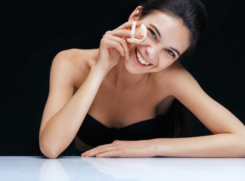 黑色的背景下微笑的女孩拿着粉扑在化妆