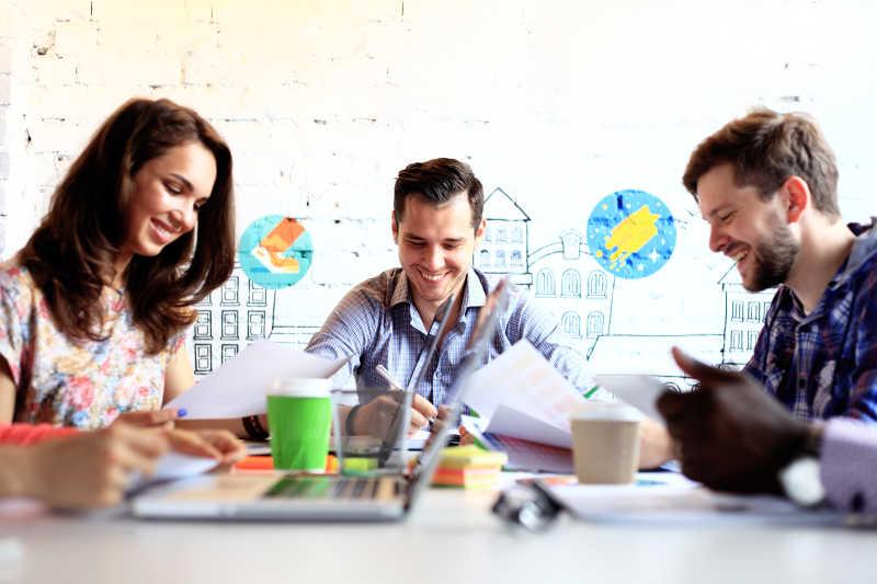 三个年轻人在办公室开心的讨论工作
