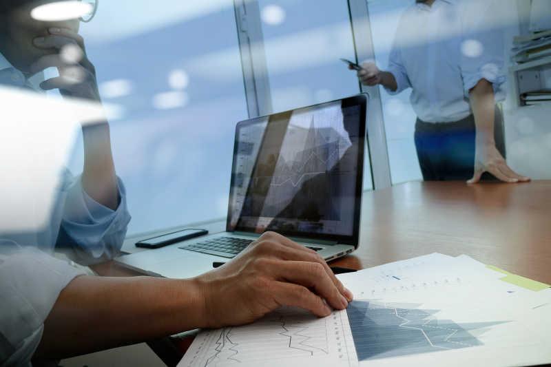 坐在笔记本电脑前研究数据的商人