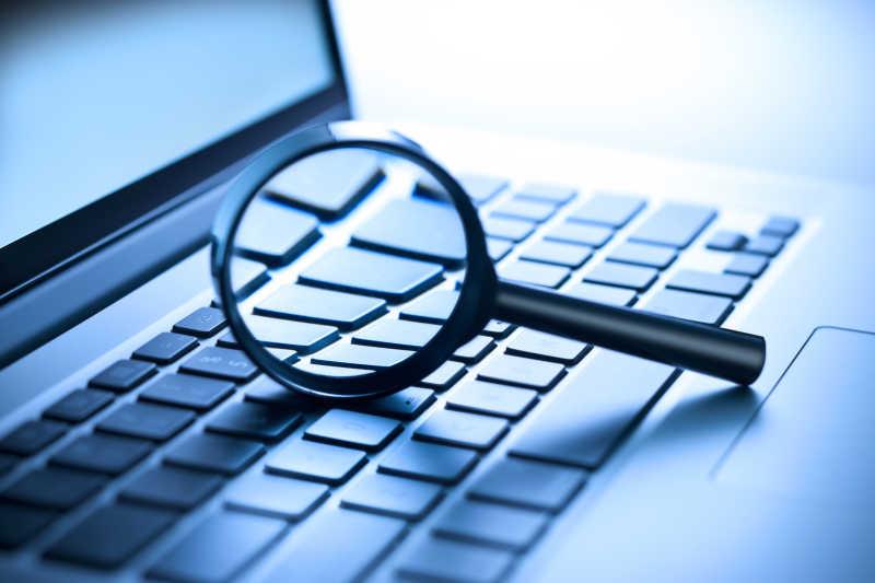电子科技笔记本电脑和放大镜