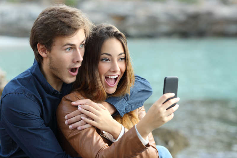 看着智能手机惊讶的夫妇