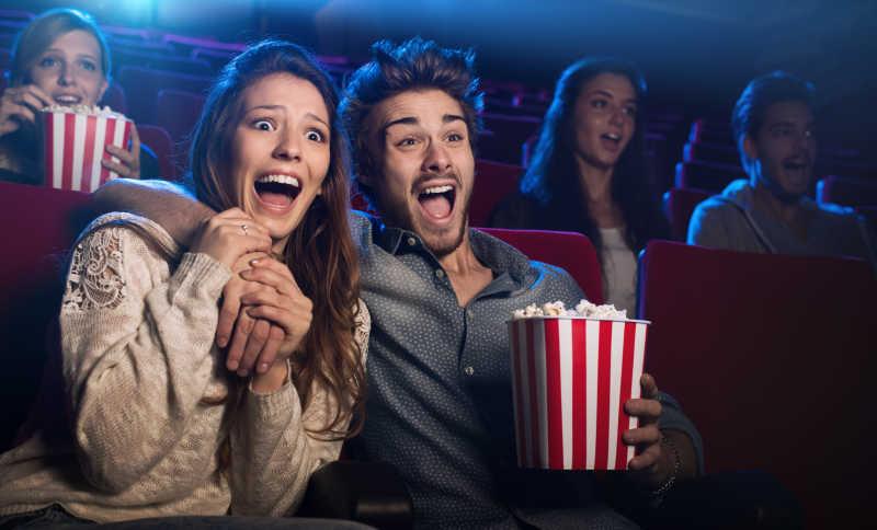 在电影院看恐怖电影的年轻夫妇