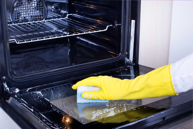 戴着黄色保护手套清洁烤箱炉门