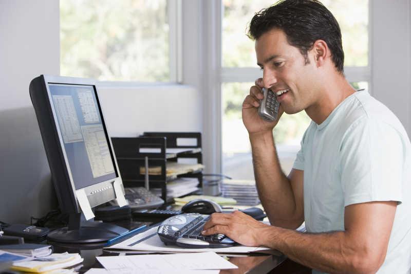 男人在电脑前打电话