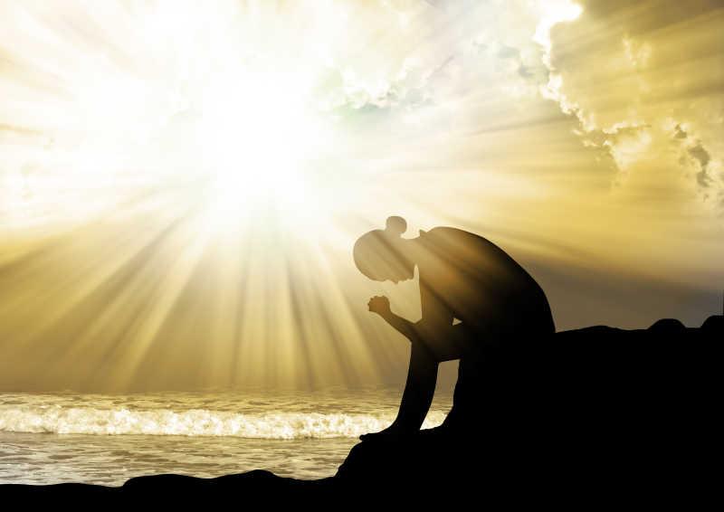日落时向着上帝祈祷的女人