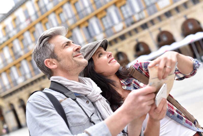 两个游客在古迹上看地图