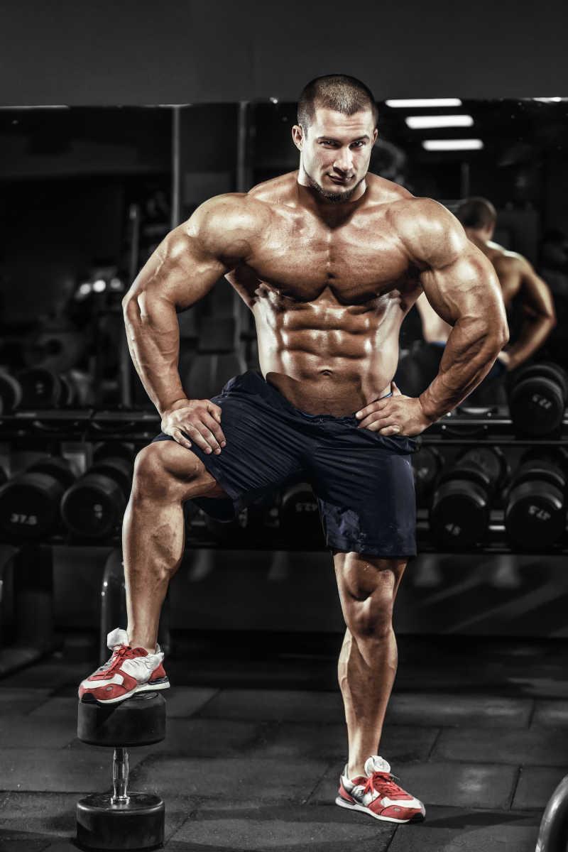 体育馆里的健美男子展示他的肌肉