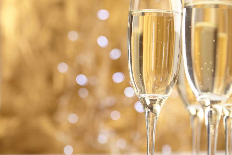 金色背景下盛满香槟的酒杯