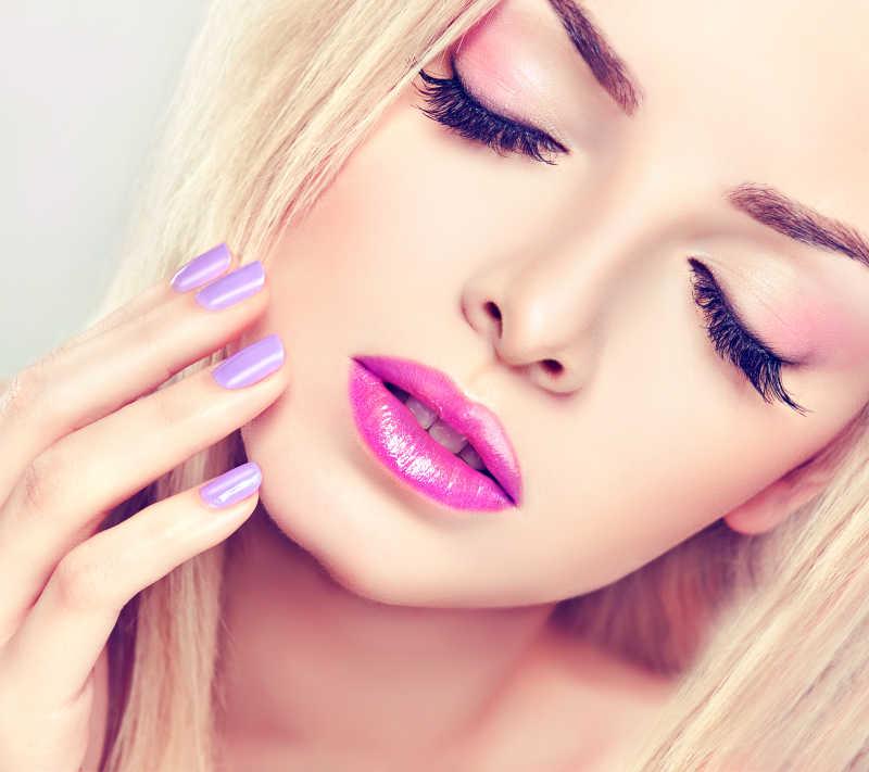 美丽的金发女孩画紫色妆容