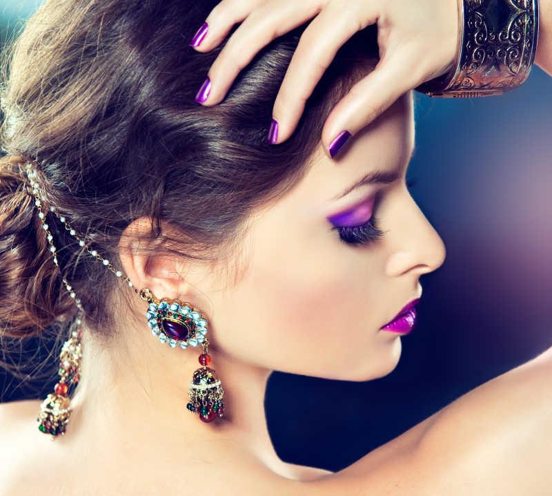 紫色化妆和修指甲的美丽模特