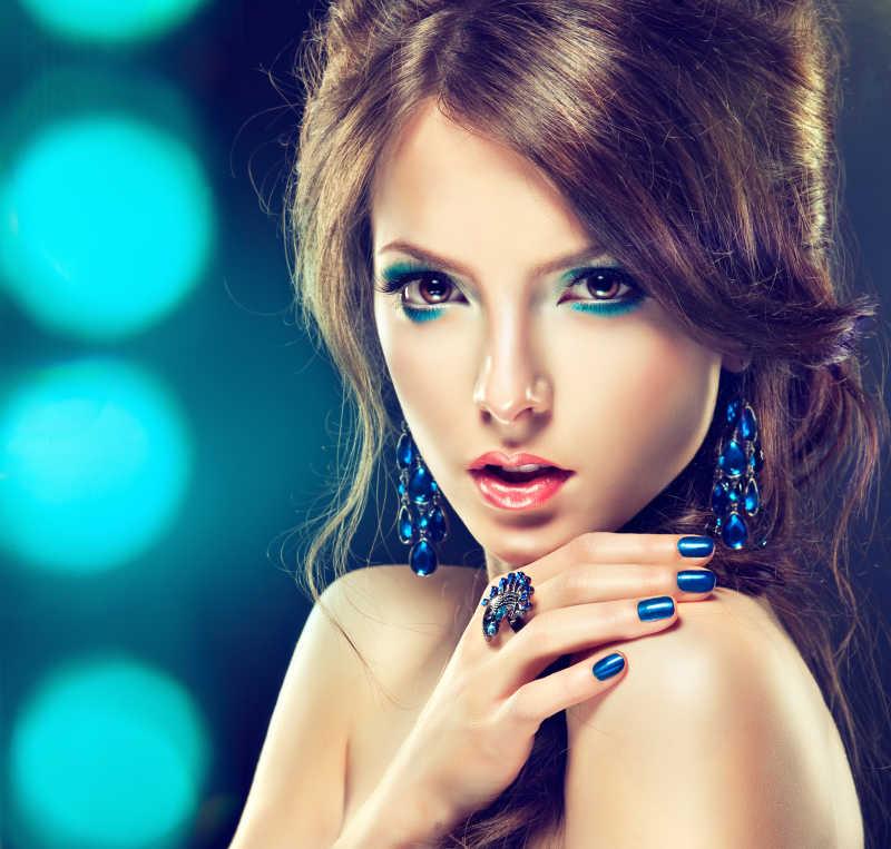蓝色化妆和修指甲的美丽女孩妆容