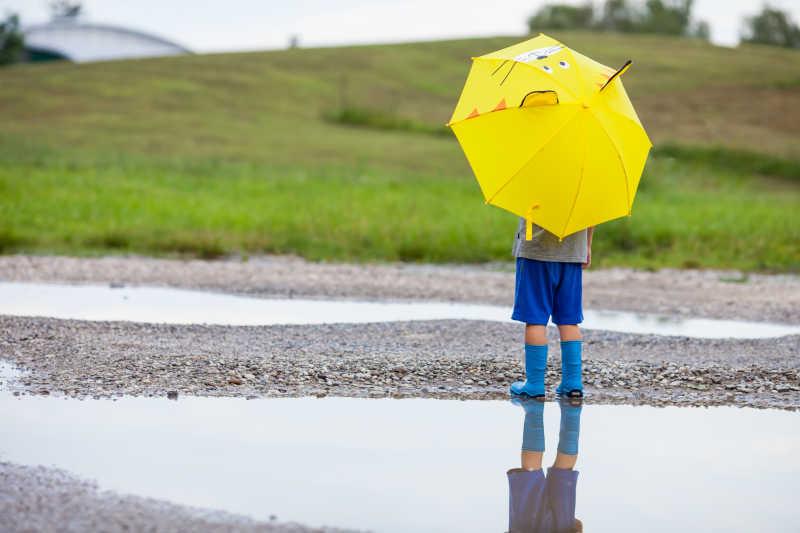 小男孩拿着黄色雨伞站在水坑旁边