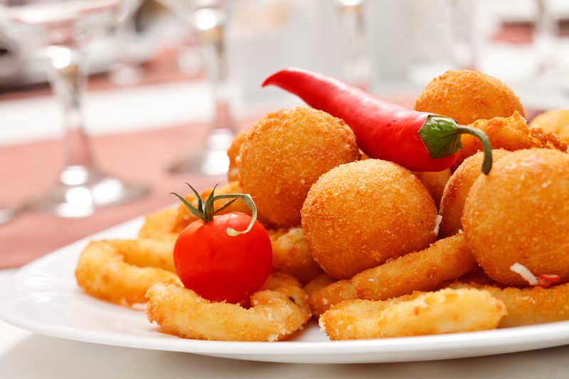 白色盘子里的炸洋葱圈和奶酪球