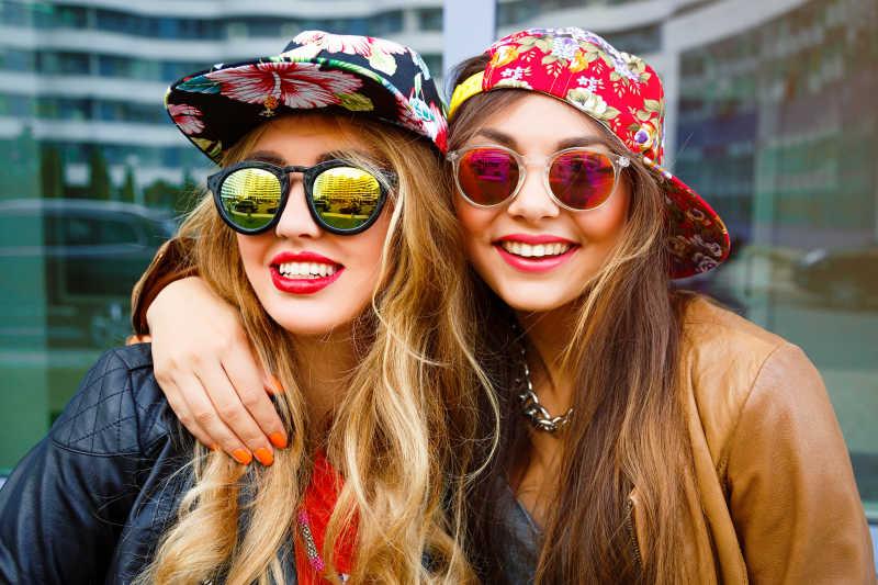 戴着帽子和眼镜的两个年轻时尚女子