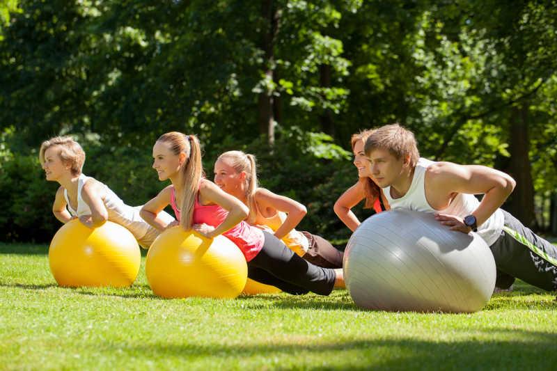 公园中年轻的人使用健身球健身