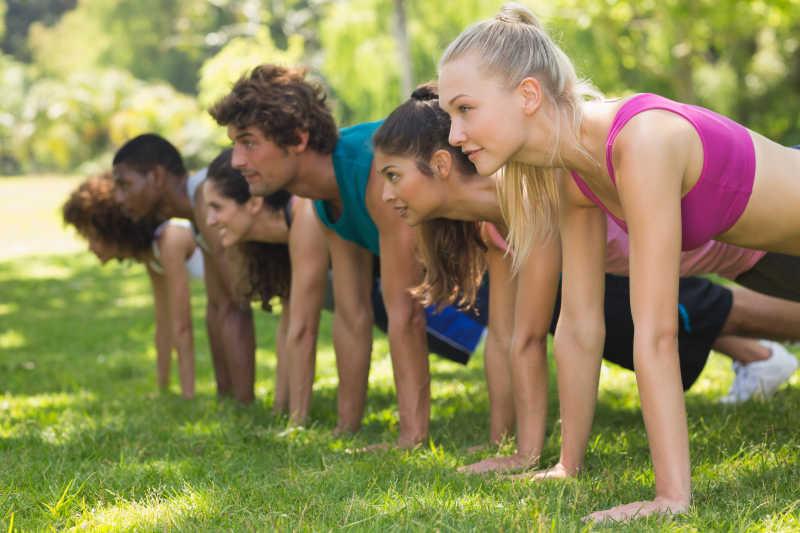 在公园里做俯卧撑的一群健身者的侧面