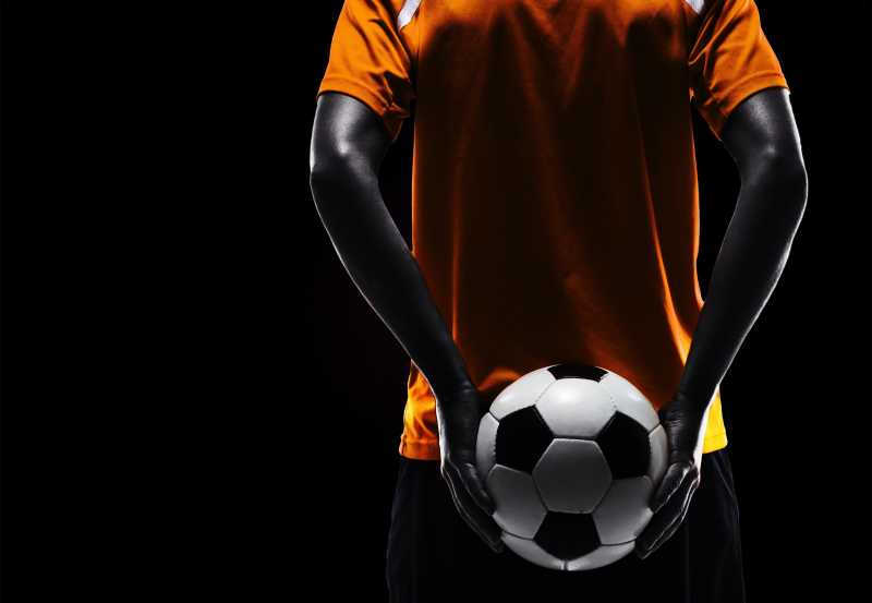 足球运动员背后的足球