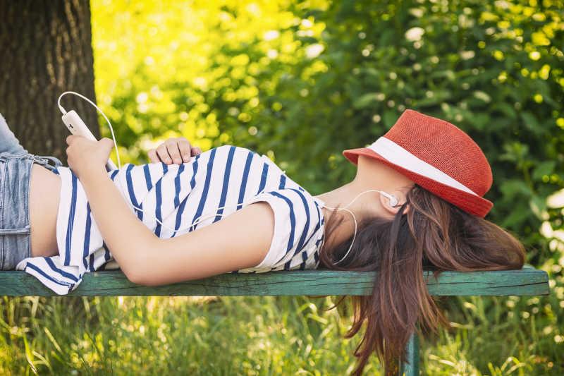 躺在长凳上听音乐的女孩