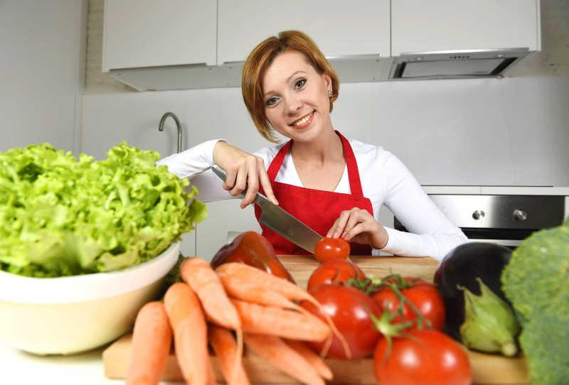 家庭厨房里快乐的女人准备做蔬菜沙拉