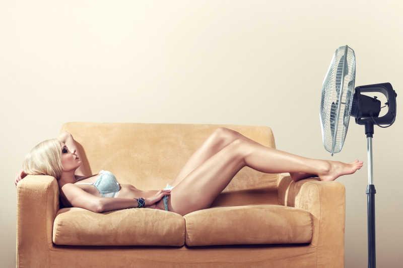 躺在沙发上用电风扇享受微风的女人