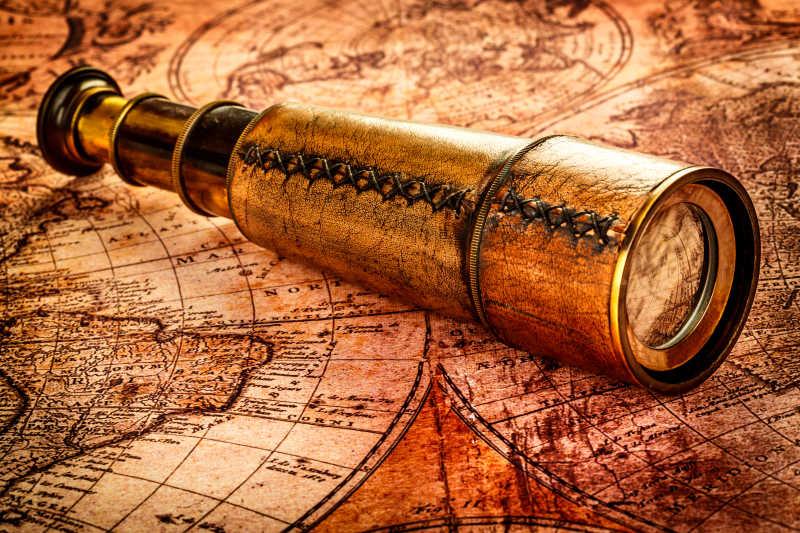 古老的世界地图上的古董望远镜