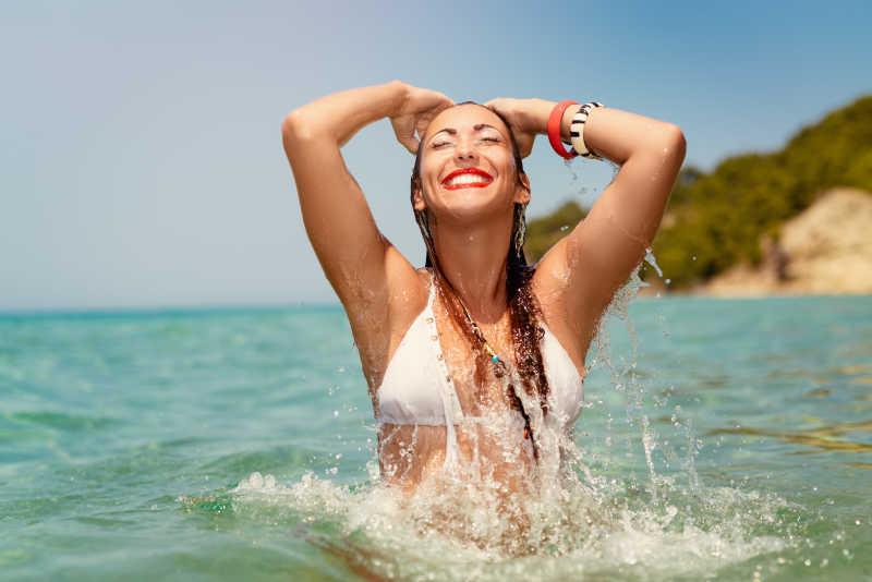 晴天海水中穿白色比基尼享受度假的美女