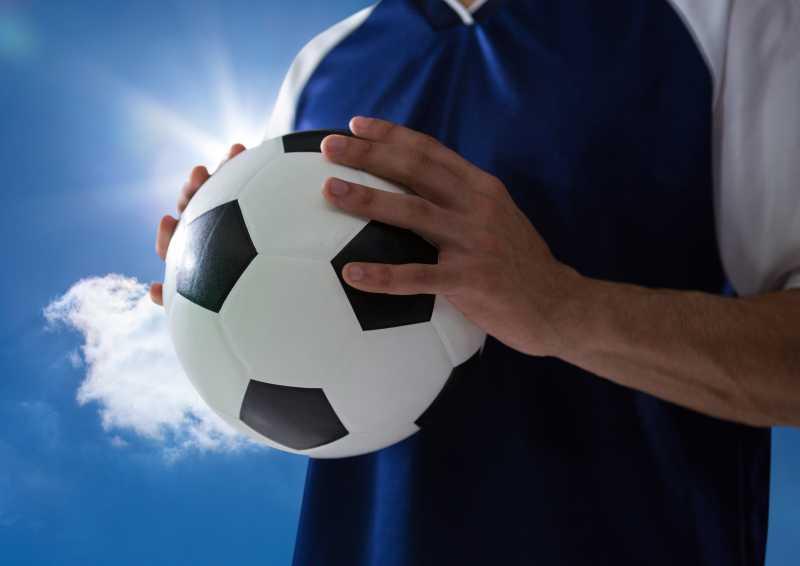 蓝天下手拿足球的男人