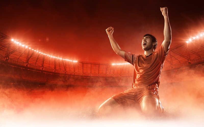 红色烟雾背景下庆祝的足球运动员