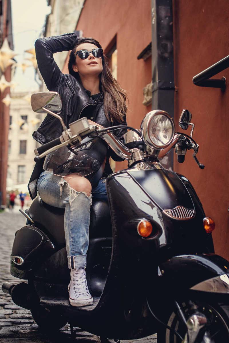 骑时尚踏板车的性感帅气的女孩