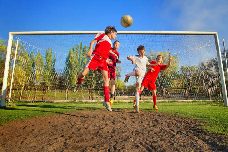 小男孩们在球门旁边的足球场上踢足球