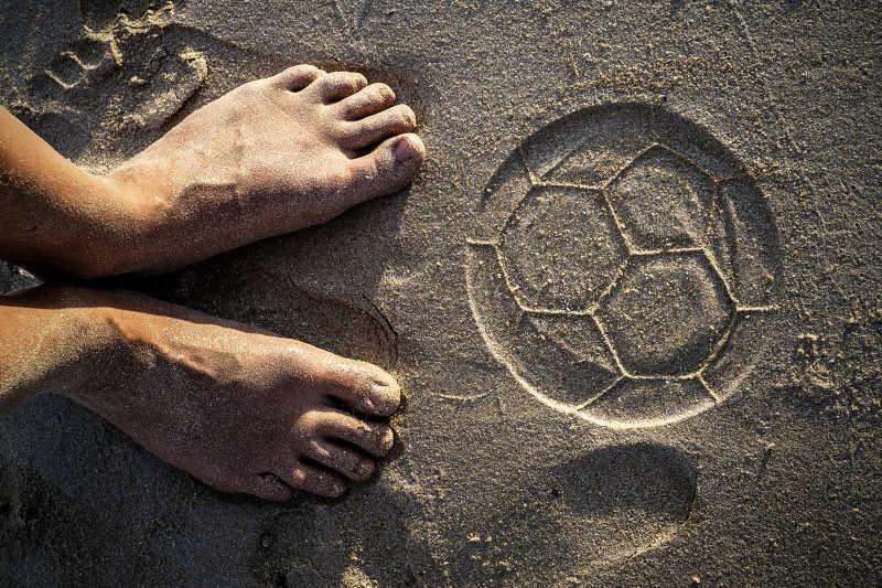 两只脚和沙滩上足球的痕迹