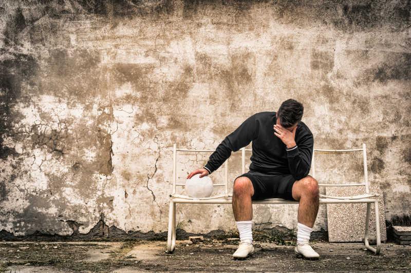 失败后的足球守门员坐在长椅上