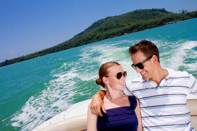 坐在游艇上的互相看着的夫妇