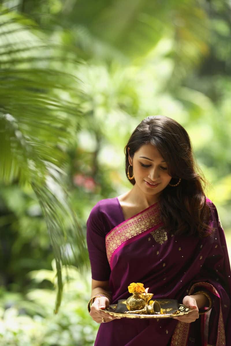 紫衣印度美女端着盘子里面放着油灯和花