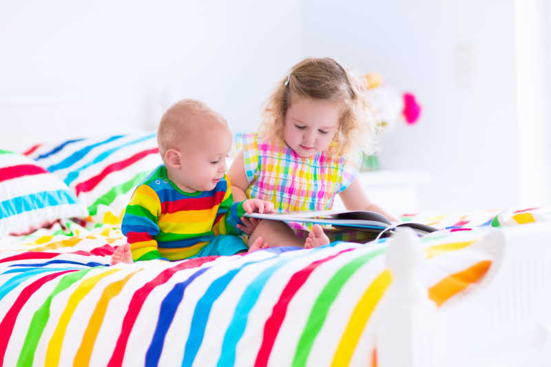 小姐弟俩坐在五颜六色的彩虹床上看书