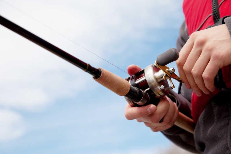 渔夫手拿鱼竿拉动卷轴收网