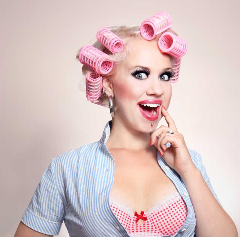 粉色背景下卷着头发的性感微笑女孩