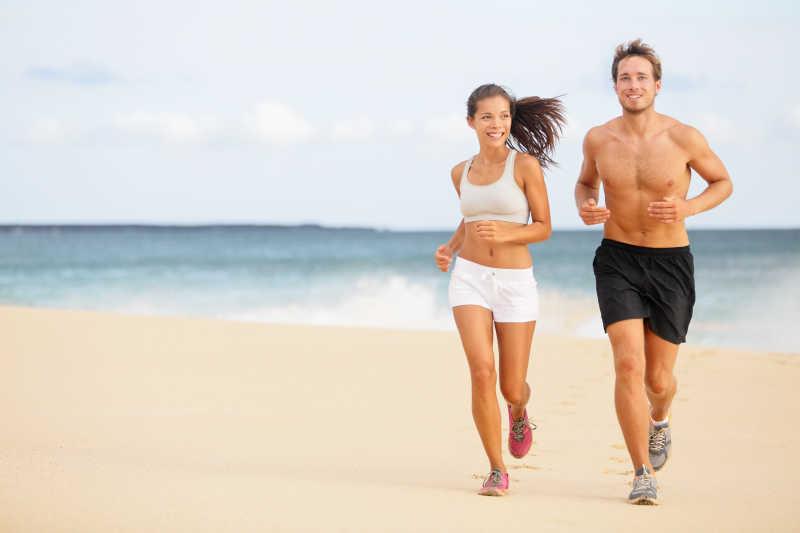 在海滩上跑步的年轻夫妇