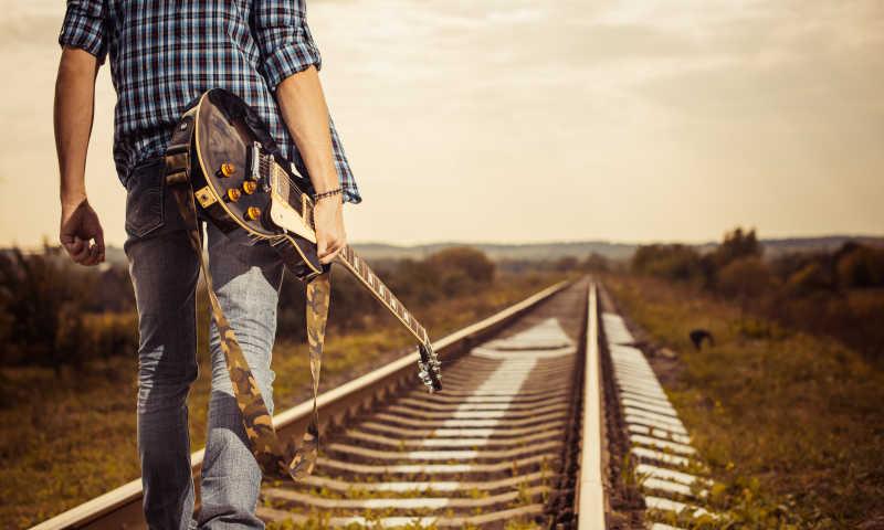 拿着吉他走在铁路上的男人
