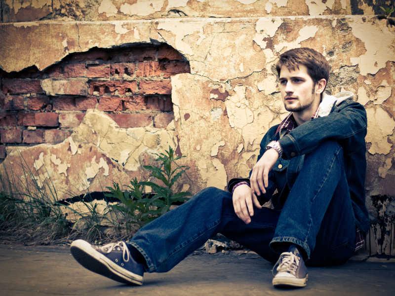 穿着牛仔裤的男人坐在地上休息