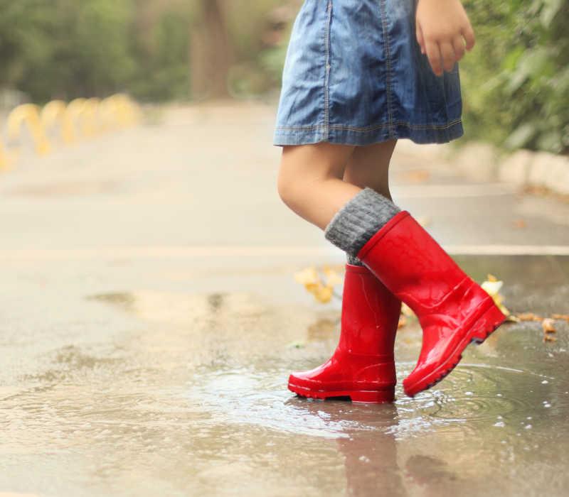 穿着红色雨靴踩在水坑里的小女孩