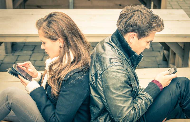 沉迷于玩手机互不关心的两个人